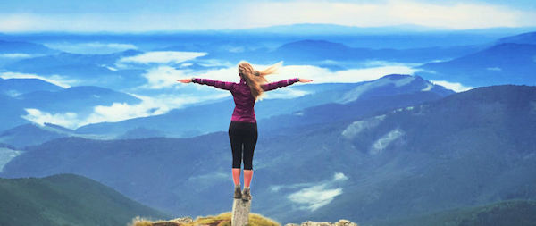 Woman standing on cliff with arms outstretched